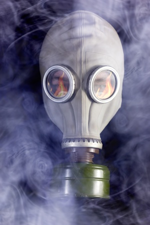 respirator: Man is in Gas Mask with Smoke around and Fire reflection Stock Photo