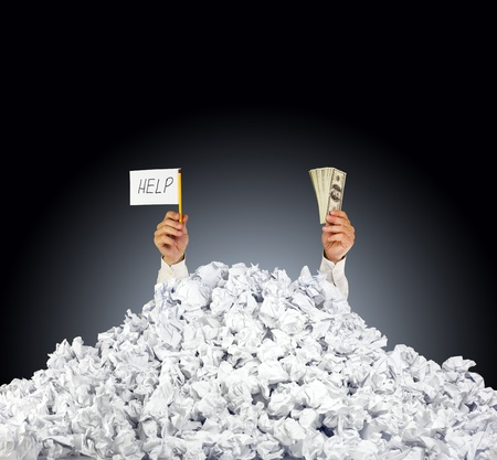 Help me! Person under crumpled pile of papers with hand holding a help sign and money  Stock Photo