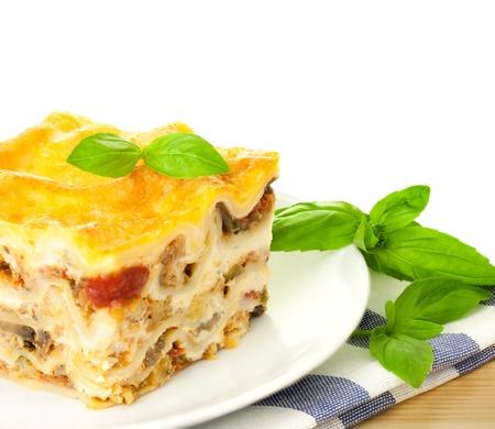 Delicious Italian Lasagna  with fresh basil  white background and copy spase  photo