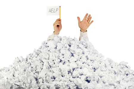 office chaos: Person under crumpled pile of papers with hand holding a help sign  isolated on white