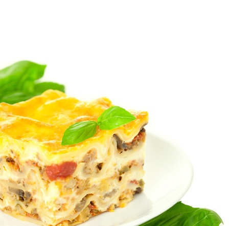 lasagna: Portion of Classic Lasagna Bolognese with basil herb  isolated on white  corner composition Stock Photo