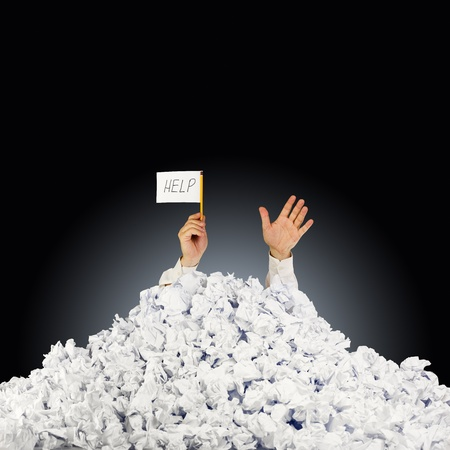 office chaos: Person under crumpled pile of papers with hand holding a help sign  Stock Photo