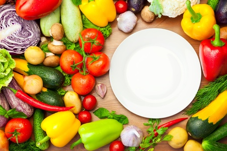 Fresh Organic Vegetables on wooden Table Around White Plate  with copy space for your text Stock Photo