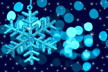 Christmas decoration snowflake  on defocused lights and stars background  blue toned photo