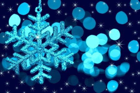 feliz: Christmas decoration snowflake  on defocused lights and stars background  blue toned