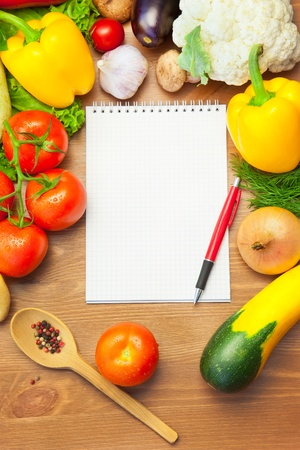Organic Vegetables on Wooden Background and Notebook for Menu or Notes photo