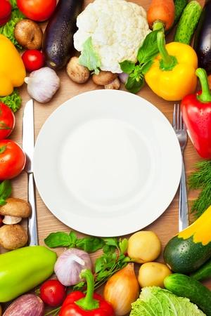 composition vertical: Fresh Organic Vegetables Circa piatto bianco con coltello e forchetta  Composizione verticale
