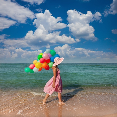 Young woman walking on the beach with colored balloons   Summer relaxations photo
