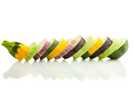 zapallo italiano: Diferentes tipos de calabacines (zucchini) y berenjenas rebanadas  colores  frontera horizontal aislado en blanco con la reflexi�n real, Foto de archivo