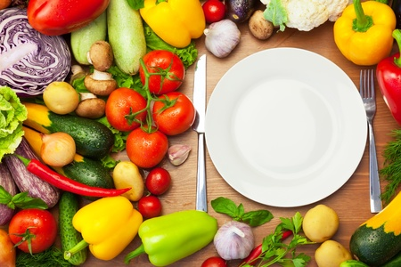 Fresh Organic Vegetables Around White Plate with Knife and Fork   copy space for text