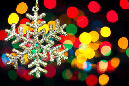Christmas decoration snowflake  on defocused lights background photo