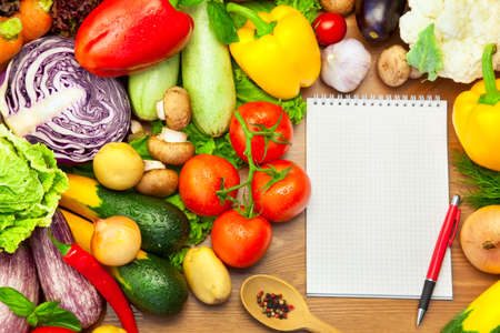 Frisches Gemüse Zusammensetzung auf dem Holzuntergrund und Notizbuch für Rezepte oder Menü Standard-Bild
