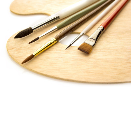 Art color brushes on wooden palette isolated on white background  photo