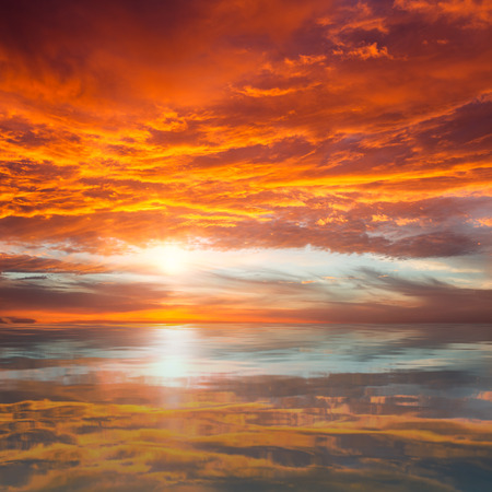 Reflection of Beautiful Sunset   Orange and Red Majestic Clouds above Water photo