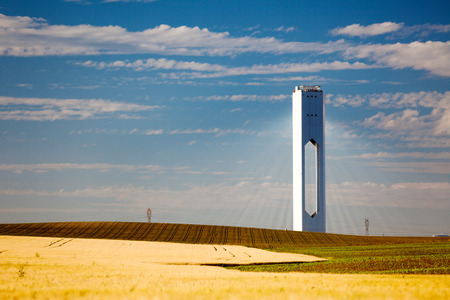 Solar Tower with rays  - thermo-solar power - blue sky and yellow field - horizontal photo