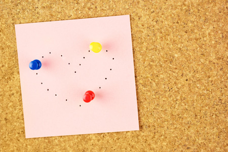 Pink sticker with heart shaped with pinholes on corkboard background photo