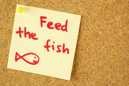 przypominać: Feed the fish remind colorful yellow sticker pined  on corkboard