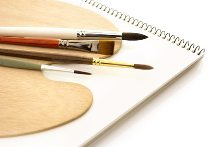 art and craft equipment: Art brushes with wooden palette and clear sketchbook isolated on white background Stock Photo
