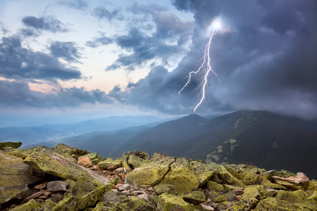 thunderstorm with lightening and dramatic clouds in Carpathian mountains photo