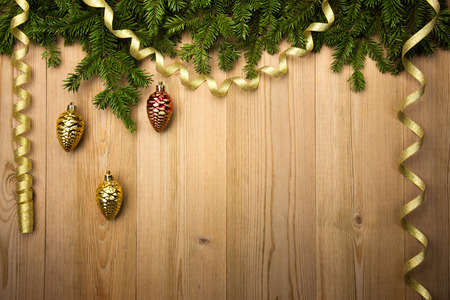 Christmas Wooden Background with fir tree, golden ribbon and decorations like pine cones photo