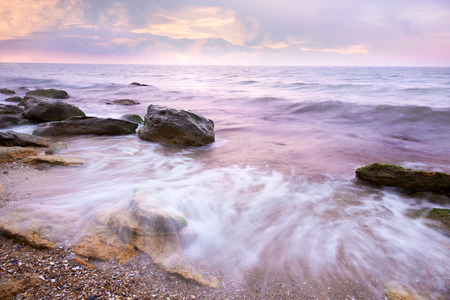 Colorful  Sunrise over the Sea and Rocky Coast ,  flowing waves  photo