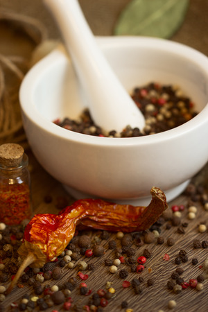 White mortar & pestle with dried pepper and chili photo