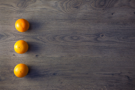 Three Oranges are on empty dark Wooden Table with copy space