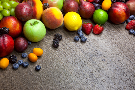 mixed fruits: Border of mixed fruits with water drops on beautiful wooden texture - copy space Stock Photo