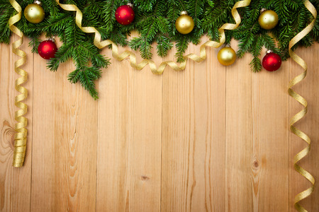 Christmas background with fresh firtree, baubles and ribbons on wood - horizontal photo