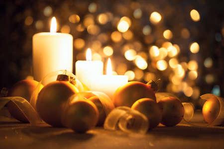 kerst interieur: Warme nacht Kerstversiering met kaarsen, ballen en linten op magische bokeh achtergrond Stockfoto
