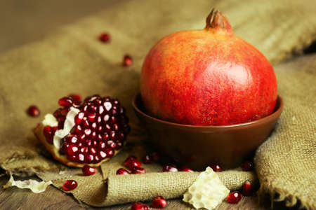 saturated color: Ripe bright red pomegranate in a bowl with seeds on wooden and sacking background