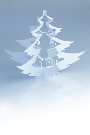 Beautiful handmade paper christmas tree silhouette on cold white background - vertical photo