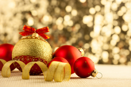 Christmas Bright red baubles with golden ribbons on bokeh background photo