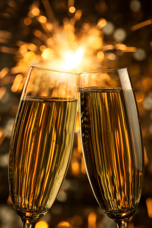 Beautiful golden champagne with sparklers on black background - vertical photo