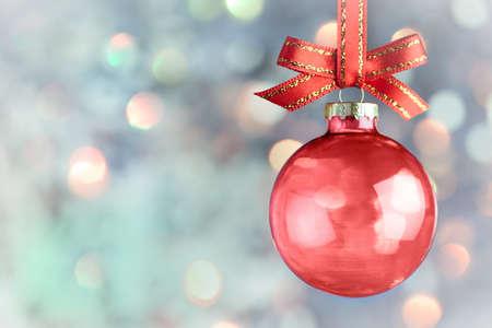 feliz: Decorazioni di Natale - Bella bokeh magico con pallina rossa e fiocco su sfondo chiaro
