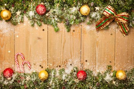 Hintergrund Weihnachten mit Tannenbaum, Süßigkeiten und Baumkugeln mit Schnee und Sterne auf Holz Standard-Bild