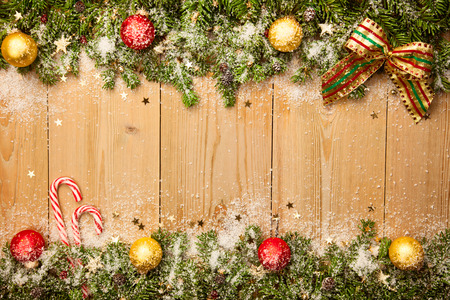 Hintergrund Weihnachten mit Tannenbaum, Süßigkeiten und Baumkugeln mit Schnee und Sterne auf Holz Lizenzfreie Bilder