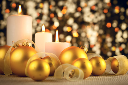 Warm Christmas glitter bokeh background with candles, baubles and ribbons photo
