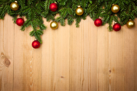 Christmas background with fresh firtree and  baubles on wood - horizontal photo
