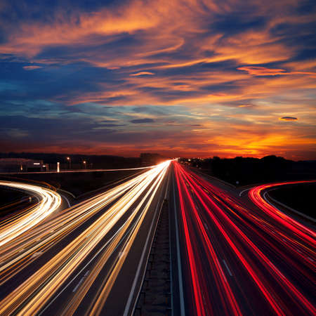 night highway: Speed Traffic at Dramatic Sundown Time - light trails on motorway highway at night,  long exposure abstract urban background Stock Photo
