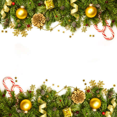 christmas gold: Christmas tree branches with golden baubles, stars, snowflakes -  border isolated on white - horizontal Stock Photo