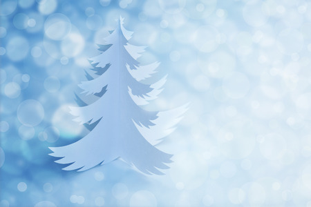 White Handmade Paper cut Christmas Tree - defocused light background with copy space for text photo