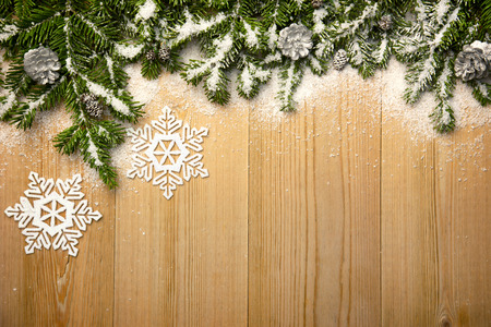 Christmas background with fresh firtree, decorative snowflakes and cones on wood with bright snow photo