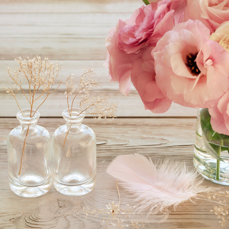 vase: Still life with pink flowers in a vase with fearher and two glass botles - vintage look
