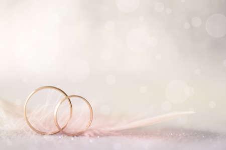 2 つの金の結婚指輪と羽 - 結婚のための光の柔らかい背景