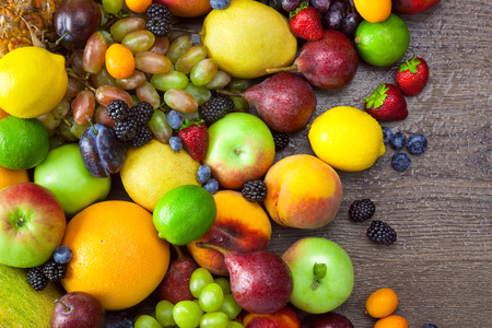 Mix of Colorful Fruits  with water drops on dark wooden table background photo