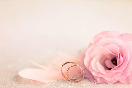 Hochzeits-Hintergrund mit goldenen Ringen, stieg Eustoma Blumen und rosa Federn Standard-Bild