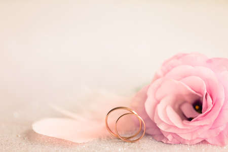 Wedding  Background with gold Rings, Eustoma rose flower and light pink feather photo