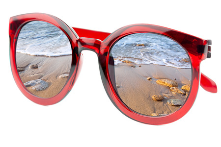 Summertime concept -  Sunglasses have a beach with wave of sea  reflecting on isolated white background photo