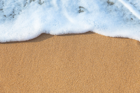 Soft wave of the sea on the sandy beach - summer background photo